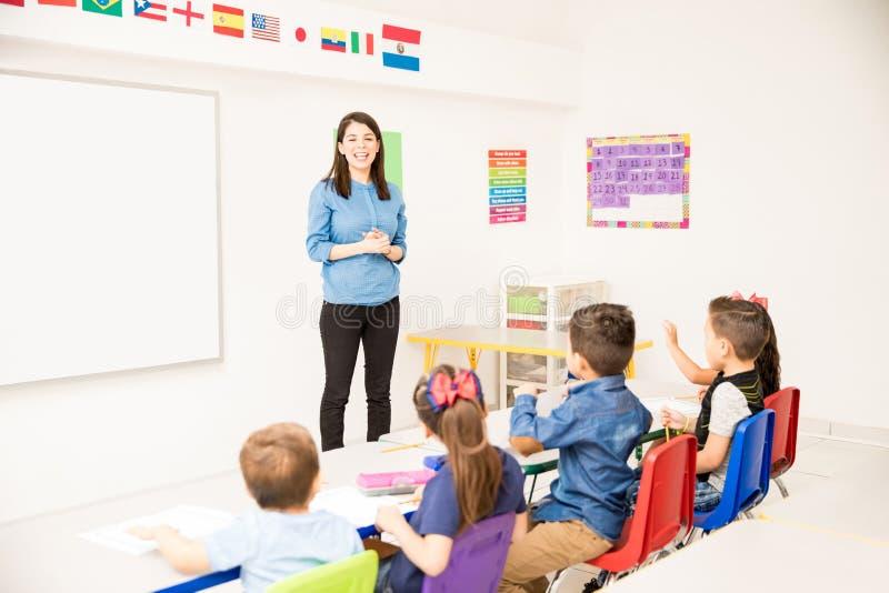 Pretty preschool teacher giving class stock image