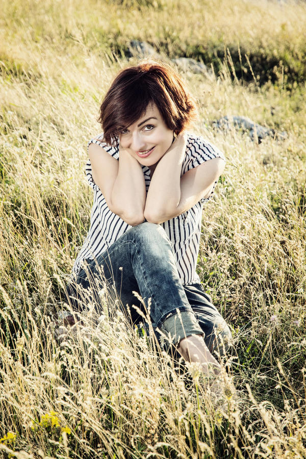 Beautiful young brunettein the meadow, female portrait stock photos