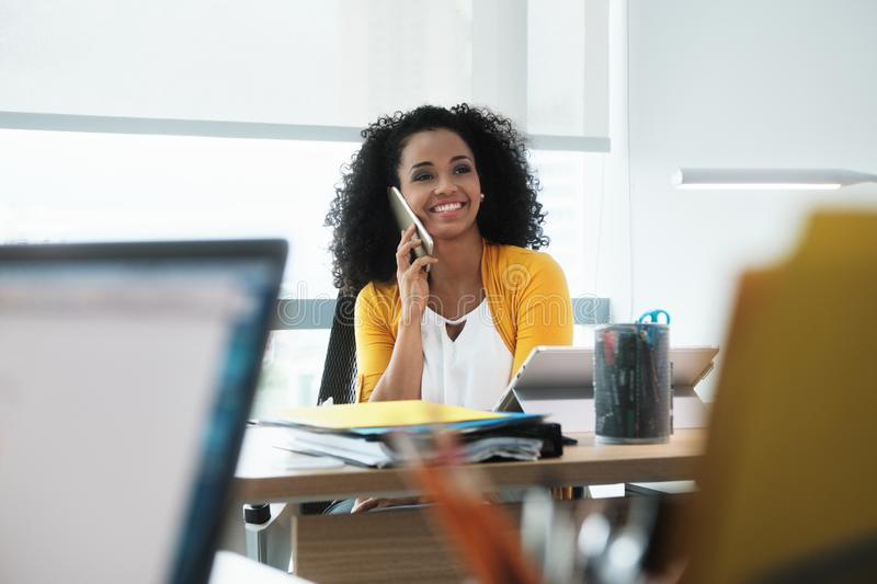 Beautiful Young Business Woman With Cell Phone In Corporate Office. Young business woman working in modern office. Black businesswoman talking and smiling on royalty free stock photo