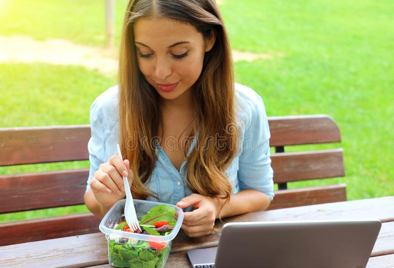 Beautiful young business woman have a lunch sitting in city park stock photography