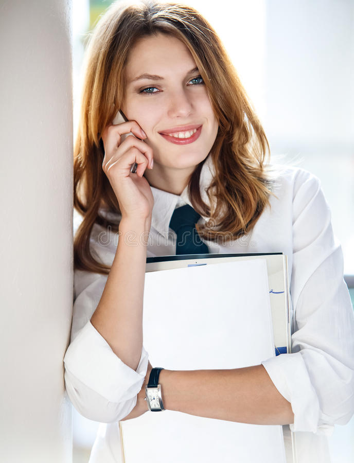 Beautiful young business woman holding folder in her hand and talking on the phone. Talkative woman in a white button down shirt with black tie royalty free stock image
