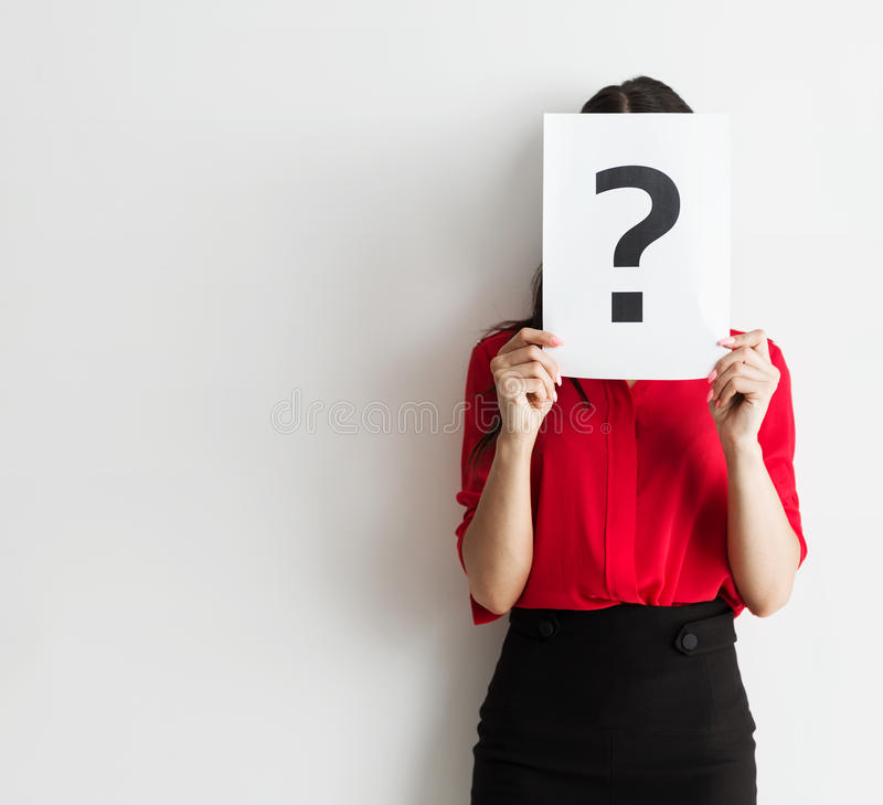 Beautiful young business woman holding a question mark royalty free stock photo