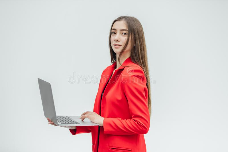Beautiful young business woman with long hair, holding a gray notebook hand, smiling, looking into the camera. Gray stock images