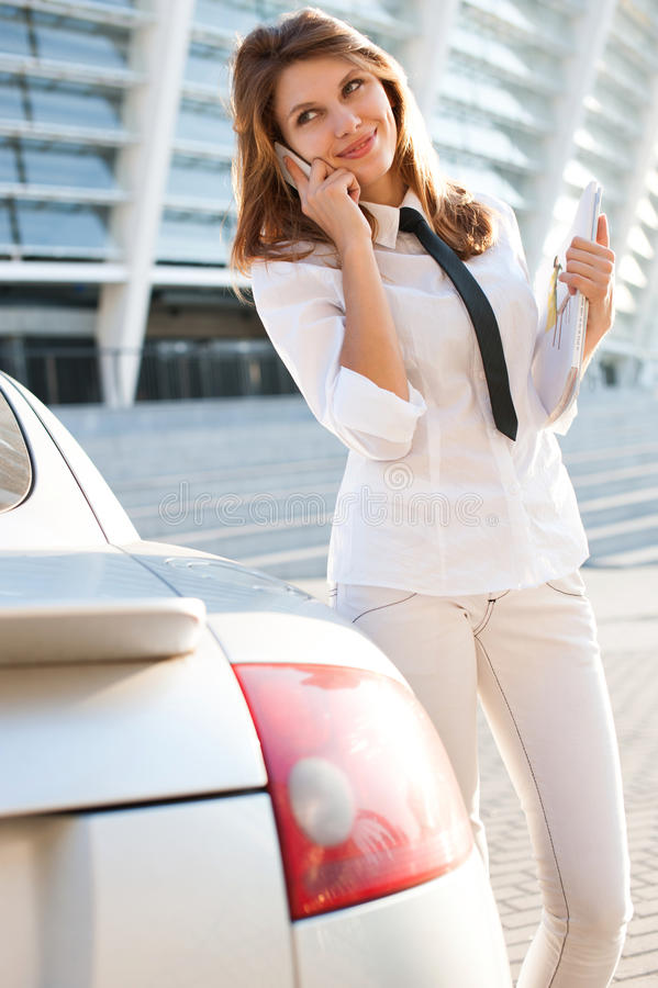 Beautiful young business woman with magazine talking on the phone. City business woman working. royalty free stock images