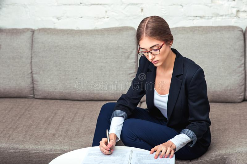 Business woman working with documents on sofa stock image