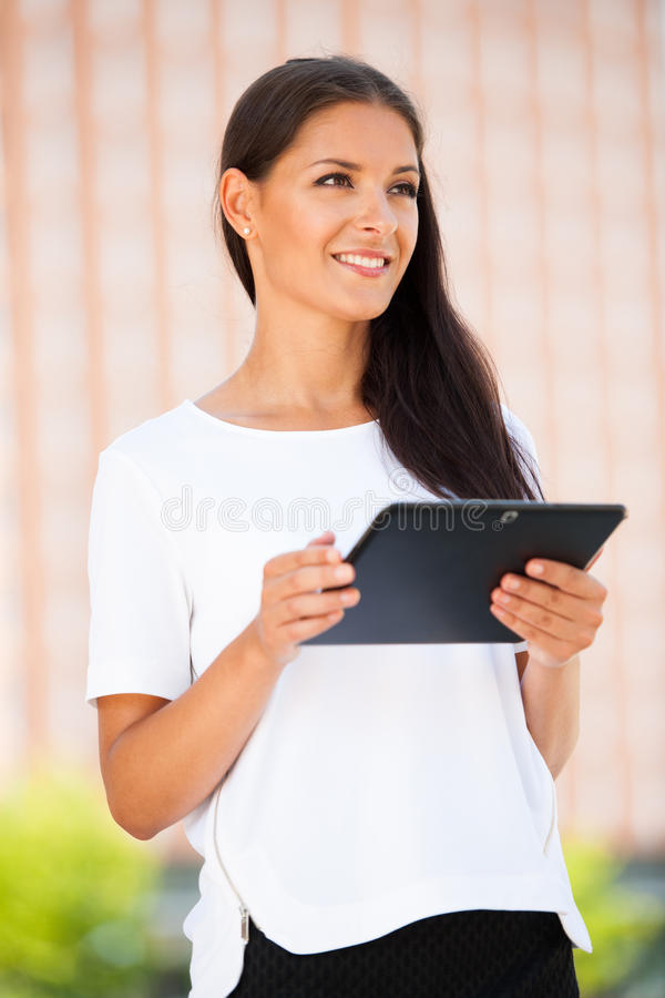 Beautiful young business woman surfing web on a tablet outdoor i stock photography