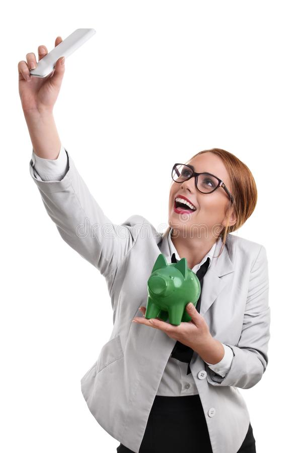 Beautiful young business woman taking a selfie with a piggy bank. Smiling beautiful young business woman dressed in a suit with glasses taking a selfie with a royalty free stock photos