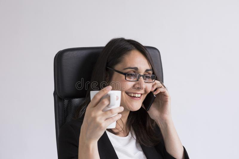 beautiful young Business woman talking on her mobile phone in the office and holding a cup of coffee. Business Concept. Lifestyle royalty free stock photos