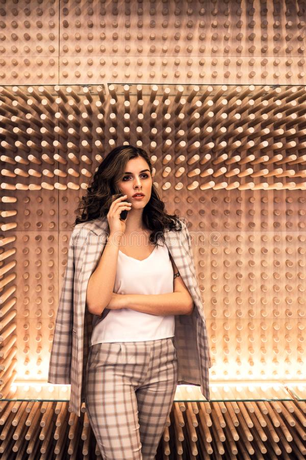 Beautiful business woman talking by phone near wooden wall. royalty free stock photos