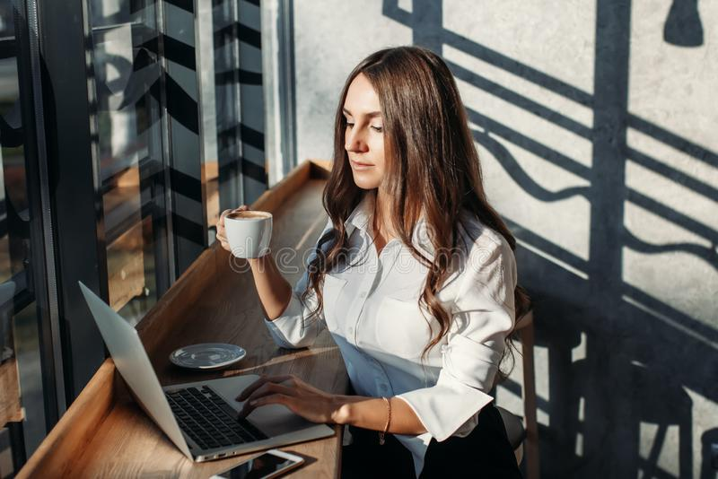 Beautiful young business woman in white blouse using laptop and smartphone, drinks coffee at a table in a cafe. Beautiful young business woman in white blouse royalty free stock image