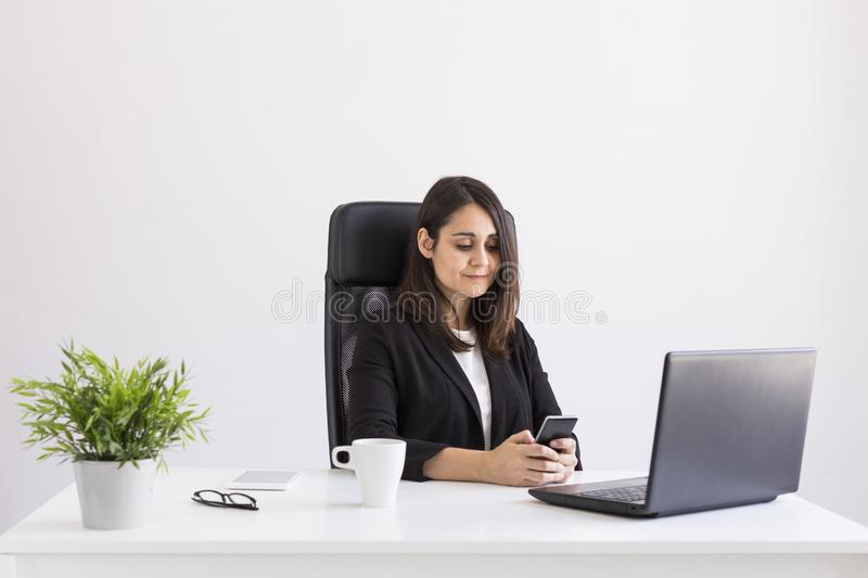beautiful young Business woman working in the office, using her laptop and mobile phone. Business Concept.white backgrounds. stock photos