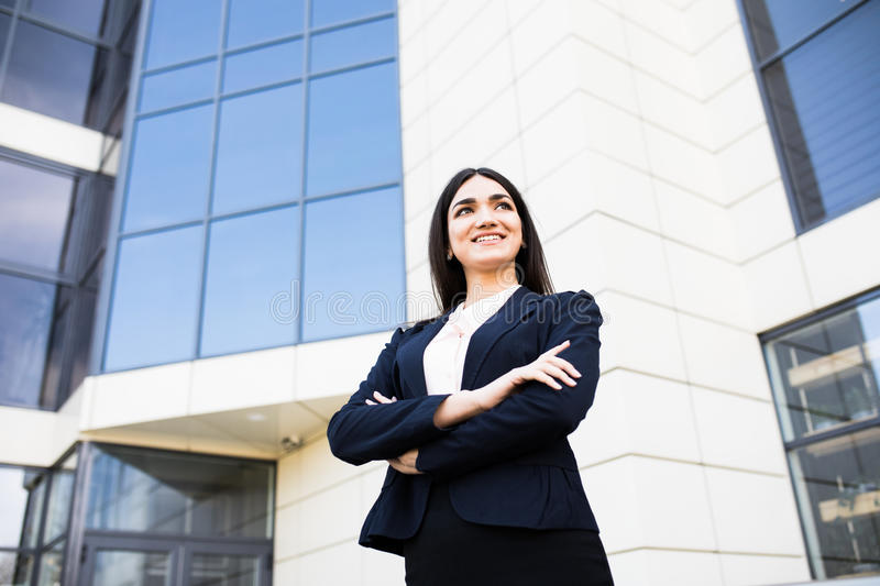 Beautiful young businesswoman against the skyscrapers of the modern business center royalty free stock image