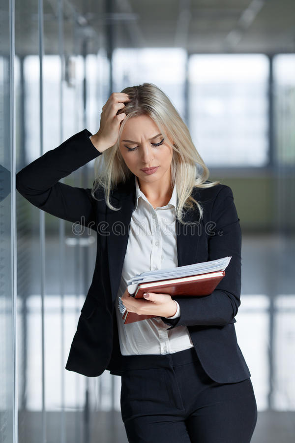 Beautiful young businesswoman angry and looking documents in the office royalty free stock photos
