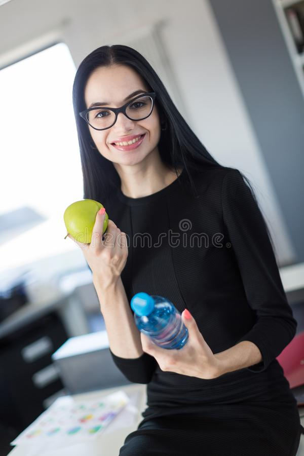 Beautiful young businesswoman in black dress and glasses sit on table in the office and hold green apple and bottle stock photography