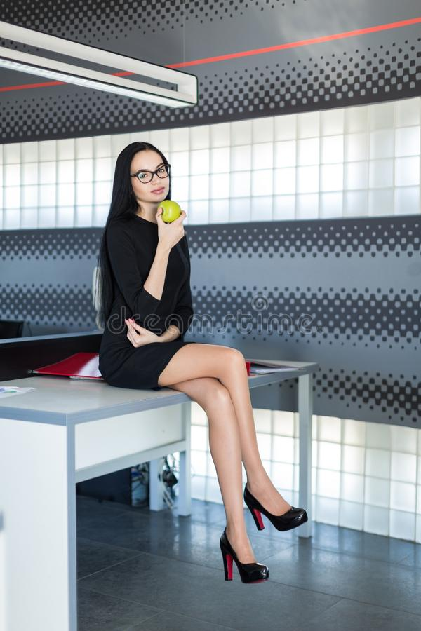 Beautiful young businesswoman in black dress and glasses sit on table in the office and hold green apple stock images
