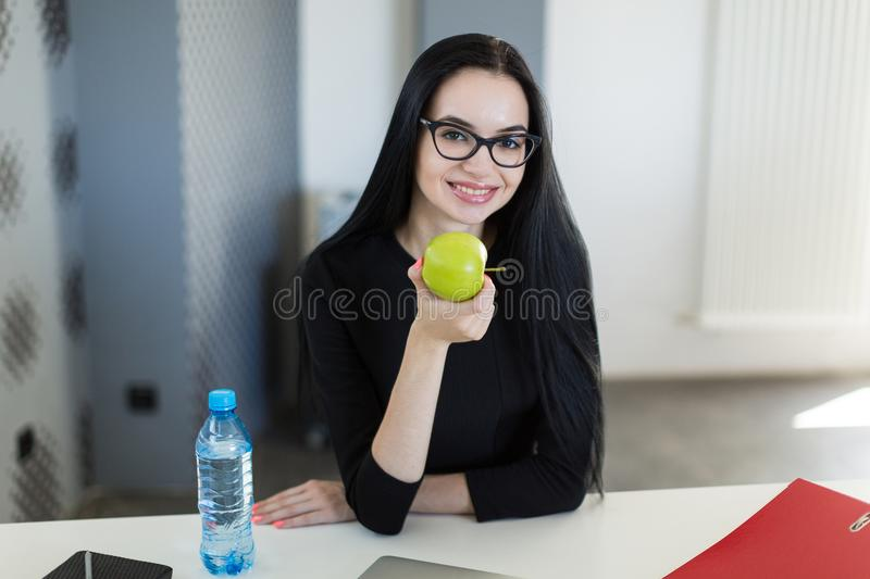 Beautiful young businesswoman in black dress and glasses sit at the table in the office and hold green apple stock image