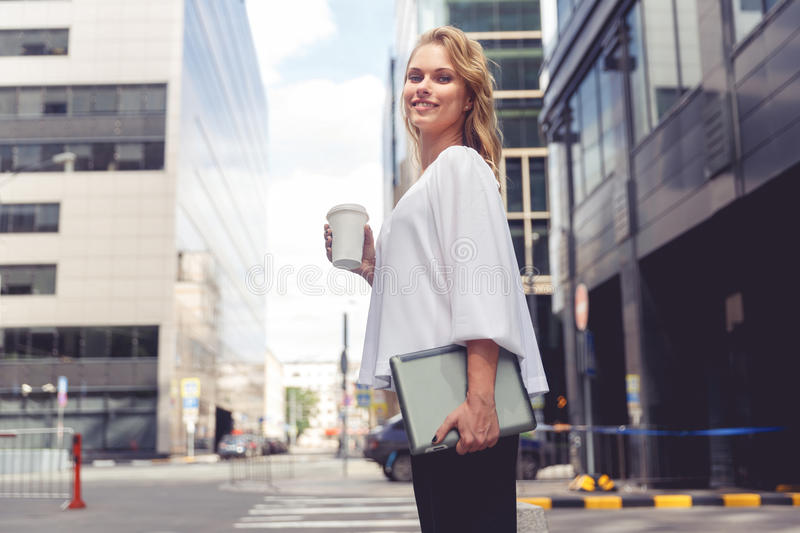 Beautiful young businesswoman with coffee holding laptop on city background stock images