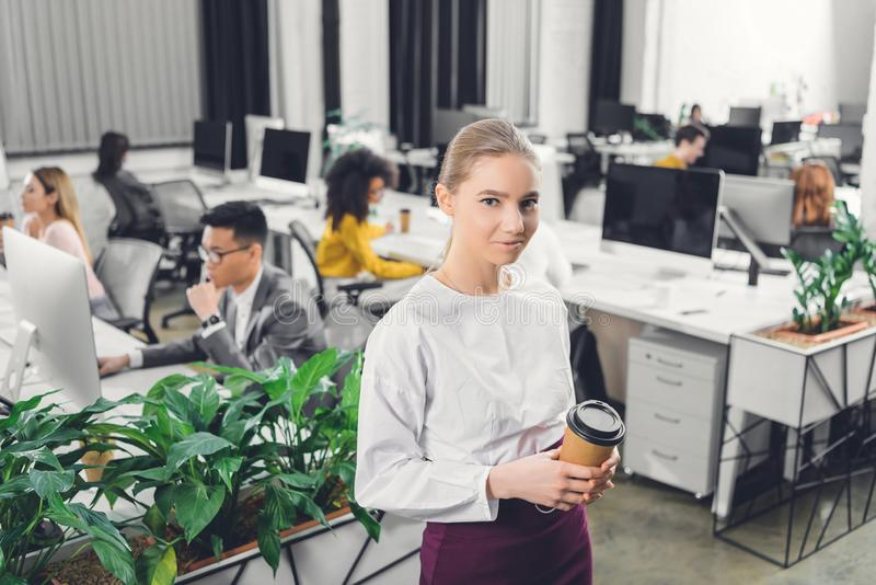 Beautiful young businesswoman holding coffee to go and smiling at camera while colleagues working behind royalty free stock image