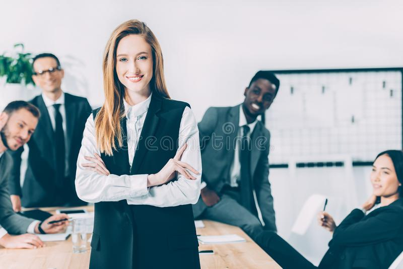 beautiful young businesswoman looking at camera with blurred multicultural colleagues royalty free stock photos