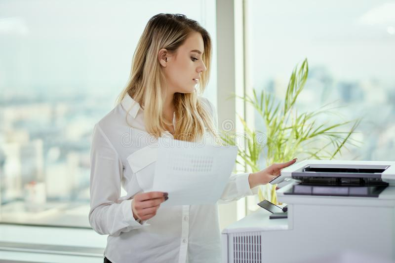 Young businesswoman prints on the printer in the office stock photo