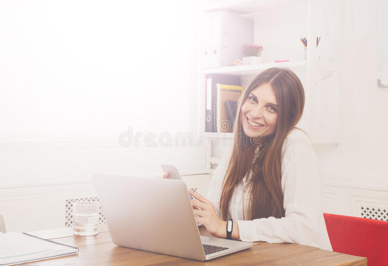 Beautiful young businesswoman sitting by office desk with laptop royalty free stock image
