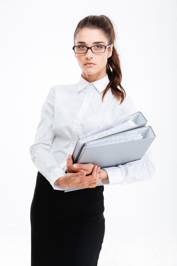 Beautiful young businesswoman standing and holding folders with documents. Beautiful young businesswoman in glasses standing and holding folders with documents stock photography