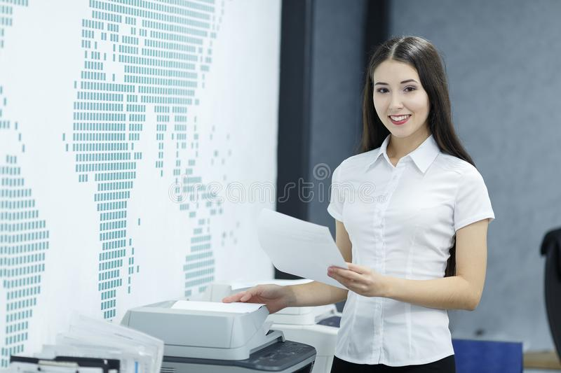 Beautiful young businesswoman using printer on table in modern office royalty free stock image