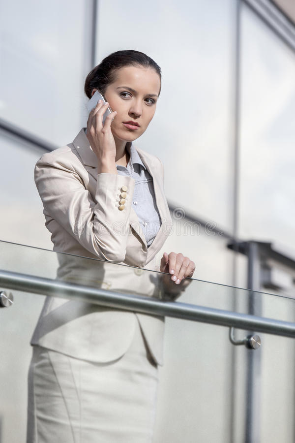 Beautiful young businesswoman using smart phone at office railing royalty free stock photography