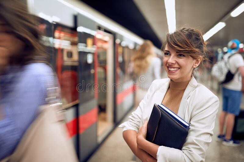 Beautiful young businesswoman waiting in line to enter in subway train, smiling royalty free stock images
