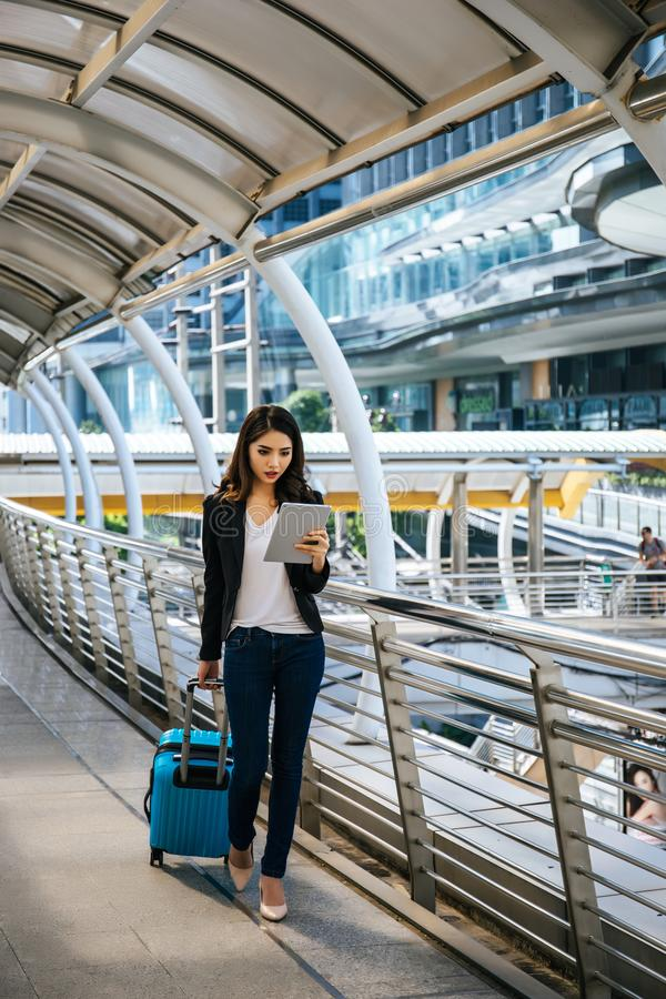 Beautiful young businesswoman walking outside public transportation station. Businesswoman traveler with suitcase on the way to. The airport royalty free stock image