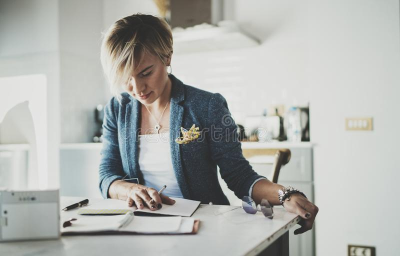 Beautiful young businesswoman writing something in note pad while sitting on armchair at living room.Charming female royalty free stock images