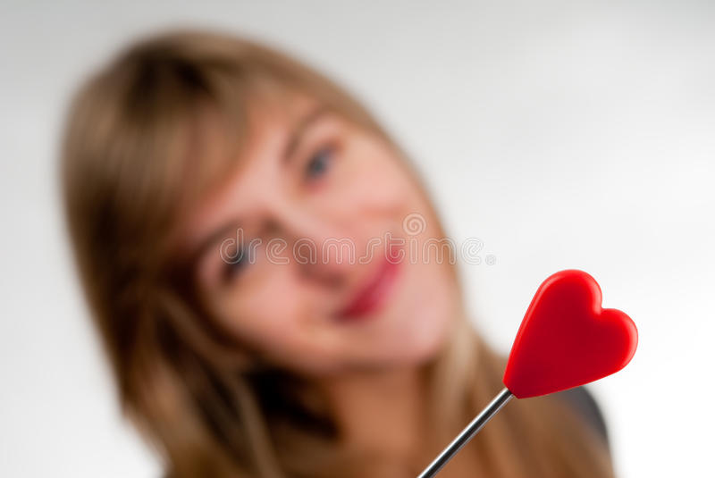 Beautiful young casual woman. Holding red heart, on white stock photography