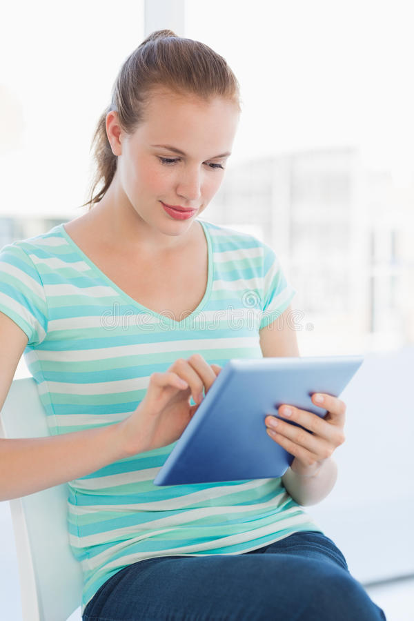 Beautiful young casual woman using digital tablet. At a bright office stock images