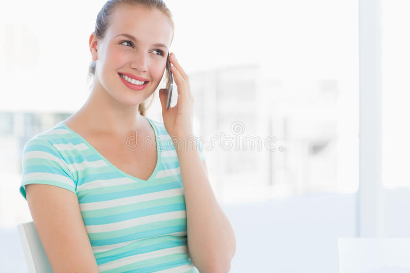 Beautiful young casual woman using mobile phone. At a bright office stock photos
