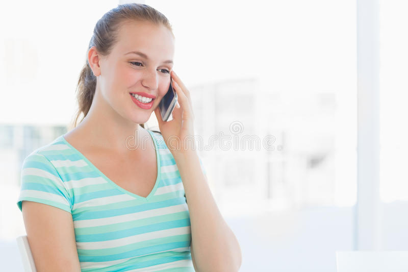 Beautiful young casual woman using mobile phone. At a bright office royalty free stock photos