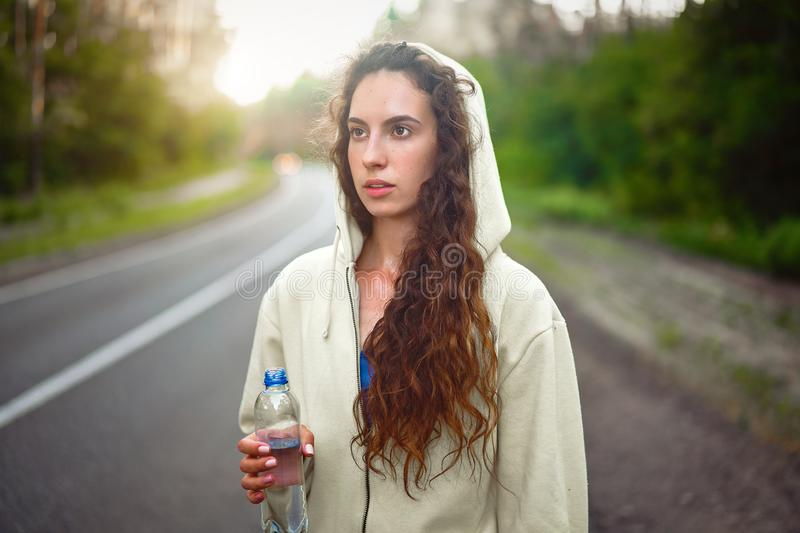 Beautiful young Caucasian girl  standing on asphalt forest road Drinks water from plastic bottle after jogging stock photos