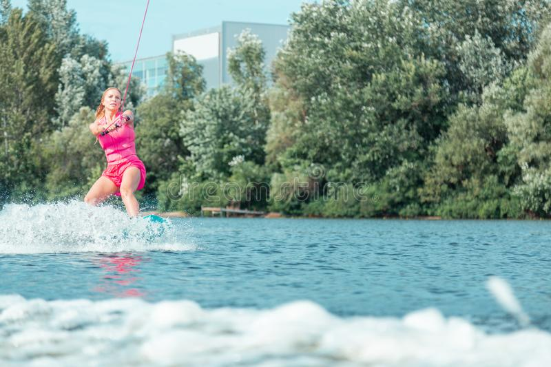 Beautiful young Caucasian girl wakeboarding on the river stock images