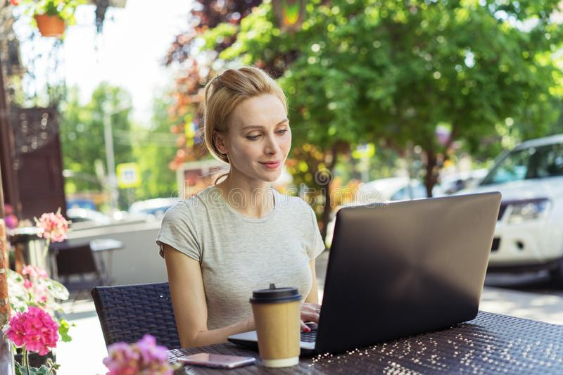Beautiful young caucasian girl working at a street coffee shop with a laptop.female freelancer royalty free stock photo