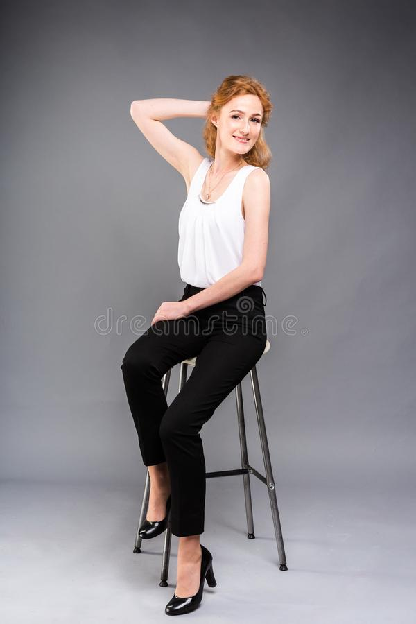 Beautiful young caucasian woman with long red hair in high heels sitting on a chair, black trousers and white shirt in stock photography