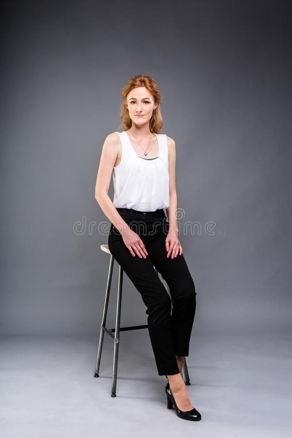 Beautiful young caucasian woman with long red hair in high heels sitting on a chair, black trousers and white shirt in stock photo