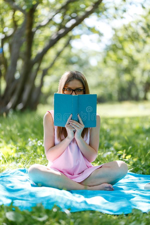 Beautiful young caucasian woman reading a book outdoor. Sitting on grass stock photos