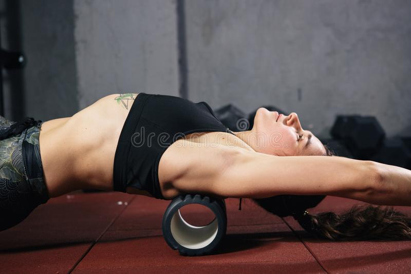 Beautiful young caucasian woman sportswoman uses a foam roller massager for relaxation, stretching muscles and back pain. Girl in stock image