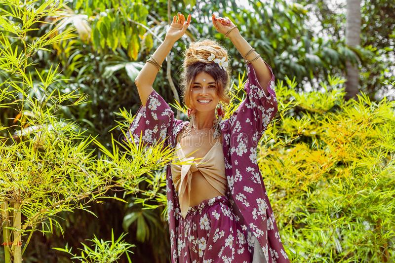 Beautiful young cheerful fashionable woman having fun at tropical background royalty free stock photography