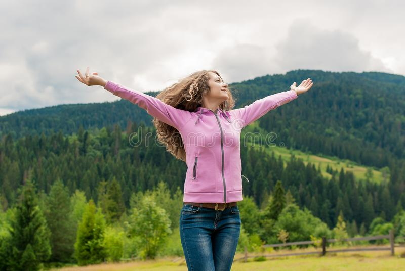 Beautiful young cheerful female model with arms up in mountains stock photos