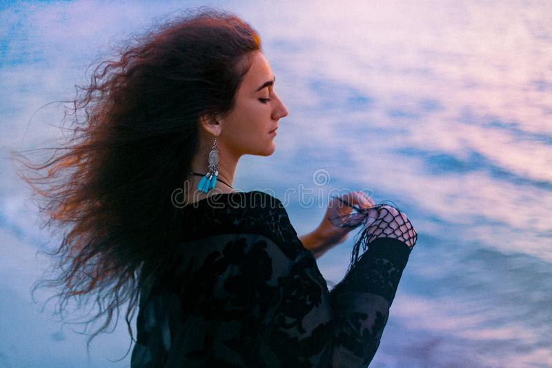 Beautiful young cheerful woman on the beach at sunset portrait stock photos