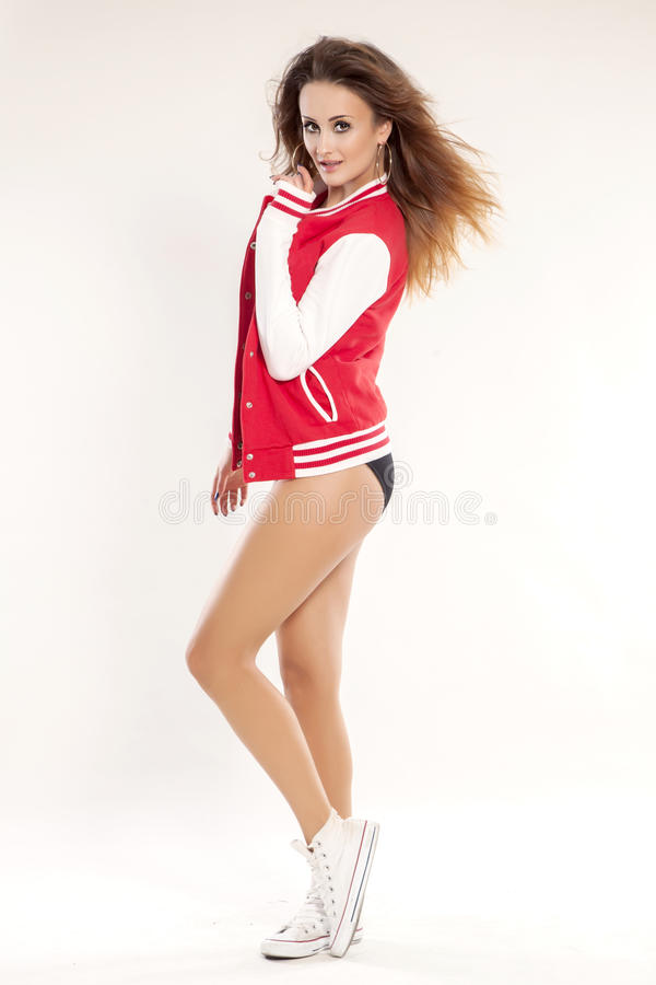 Beautiful young cheerleader in a red uniform stock images