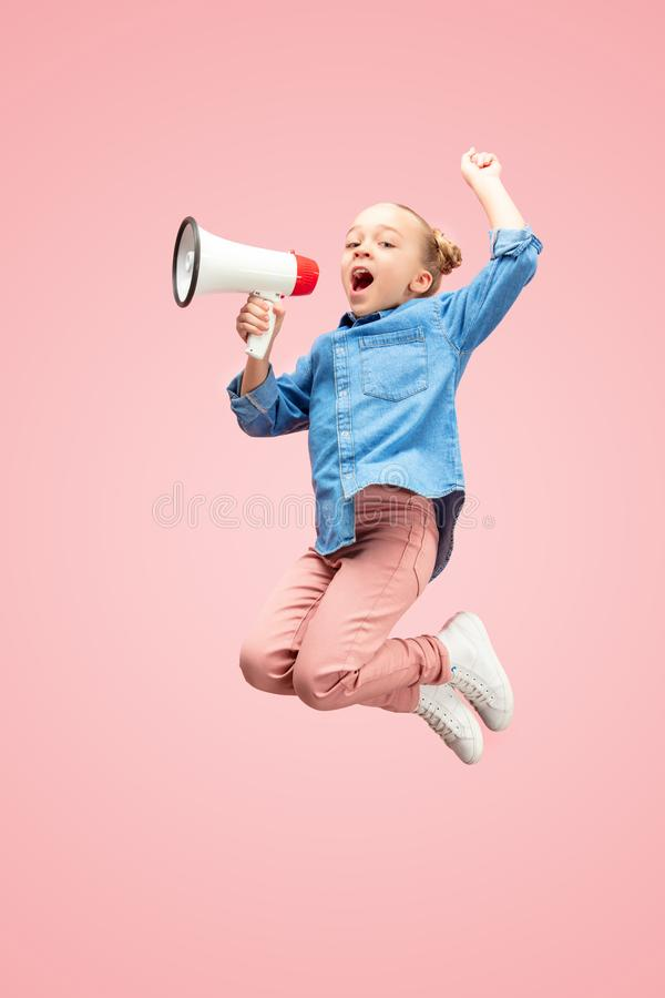 Beautiful young child teen girl jumping with megaphone isolated over pink background royalty free stock photo