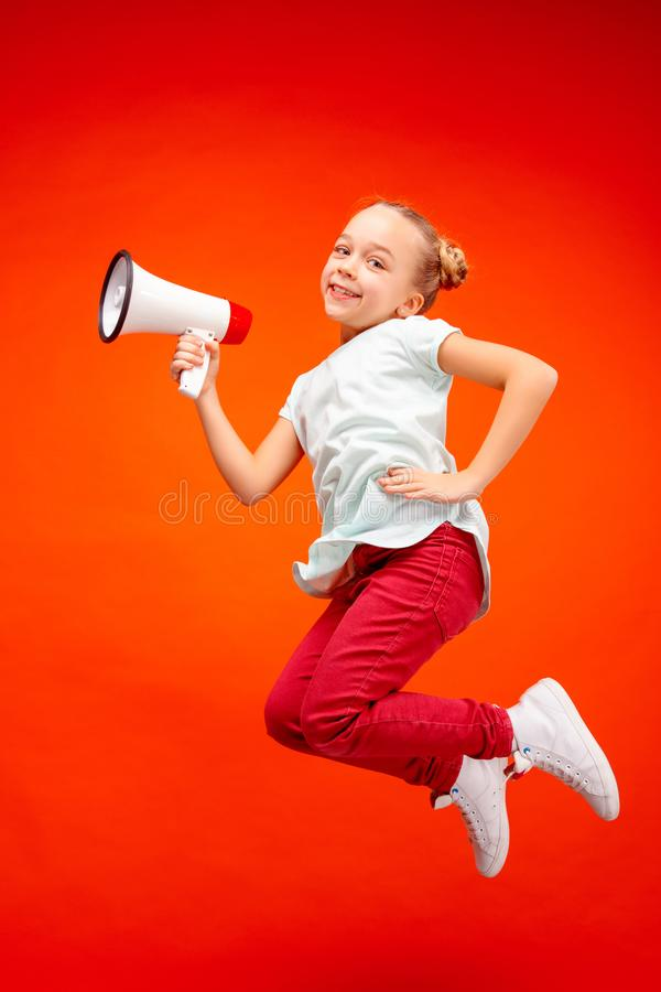 Beautiful young child teen girl jumping with megaphone isolated over red background. Runnin girl in motion or movement. Human emotions,, facial expressions and royalty free stock photography
