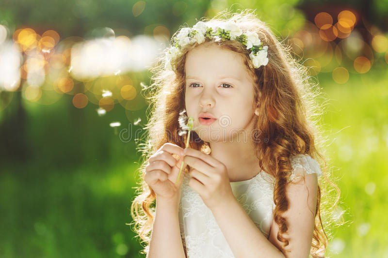 Beautiful young child on white dress blowing a dandelion in spring park. royalty free stock images