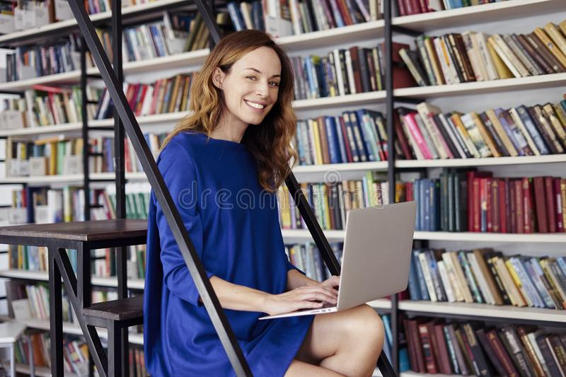 Beautiful young college student sitting on stairs in the library, working on laptop. Woman wearing blue dress, huge bookshelf stock image